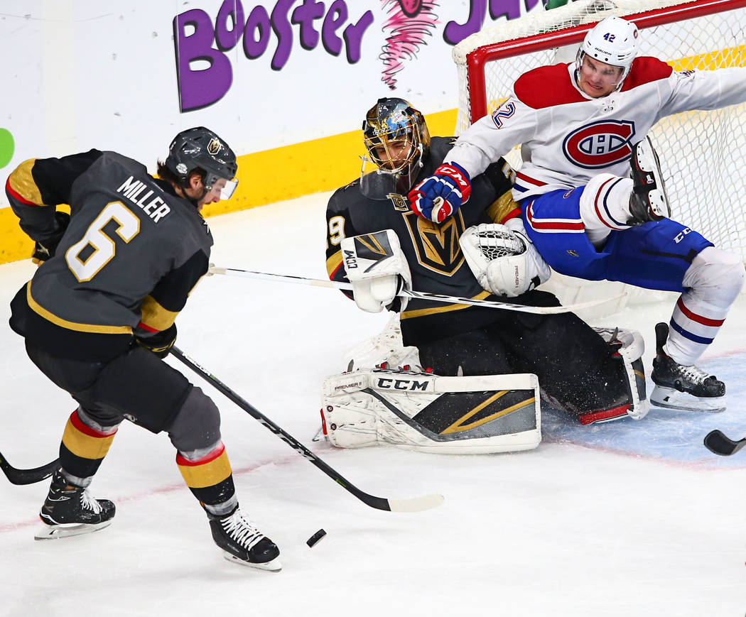 Montreal Canadiens center Byron Froese (42) falls onto Golden Knights goaltender Marc-Andre Fleury (29) as Golden Knights defenseman Colin Miller (6) goes for the puck during an NHL hockey game at ...