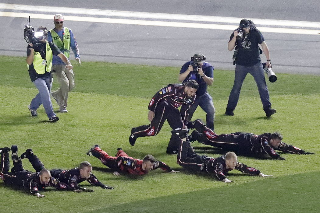 Austin Dillon, center, celebrates with his crew as they dive on the grass in the infield after winning the NASCAR Daytona 500 auto race at Daytona International Speedway, Sunday, Feb. 18, 2018, in ...