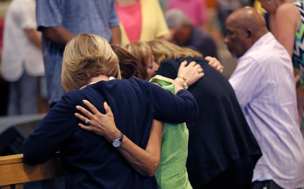 People embrace during a service at the First United Methodist Church in Coral Springs, Fla., on Sunday, Feb. 18, 2018. The service was dedicated to the victims of Wednesday's mass shooting at near ...