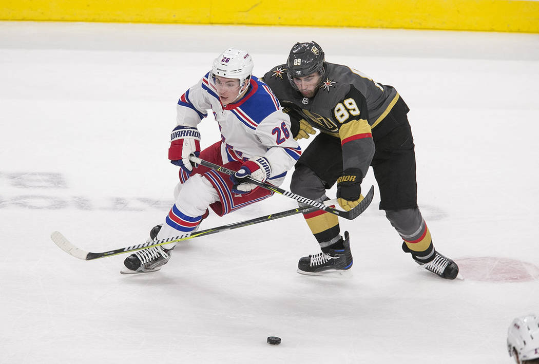 New York Rangers left wing Jimmy Vesey (26) and Vegas Golden Knights right wing Alex Tuch (89) vie for the puck during the third period of an NHL hockey game between the Vegas Golden Knights and t ...