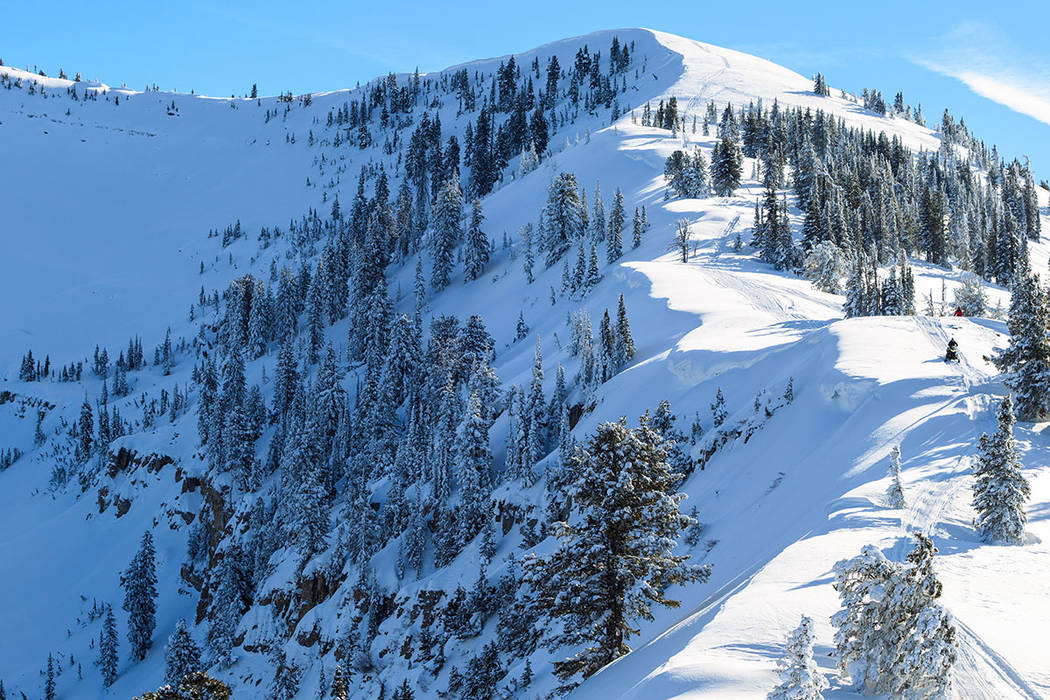 A snowmobile rides on a ridge (Thinkstock)
