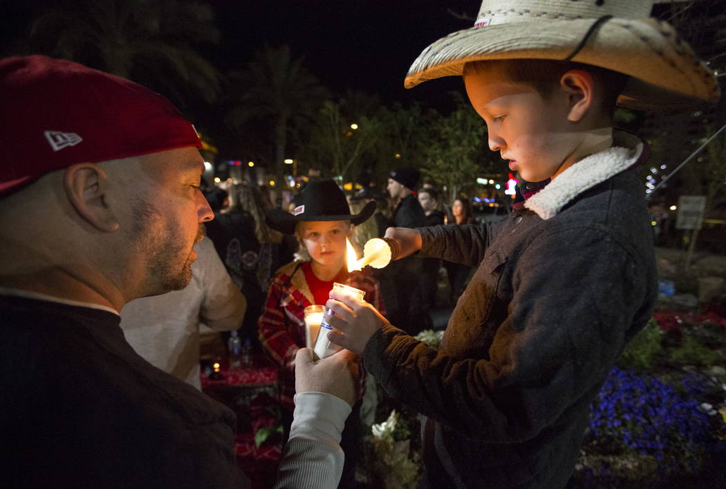 Michael Hrustyk, from left, lights candles with his children Jackson, 6, and Reagan, 9, during a candlelight vigil at the Las Vegas Community Healing Garden on Friday, Feb. 16, 2018, to honor vict ...