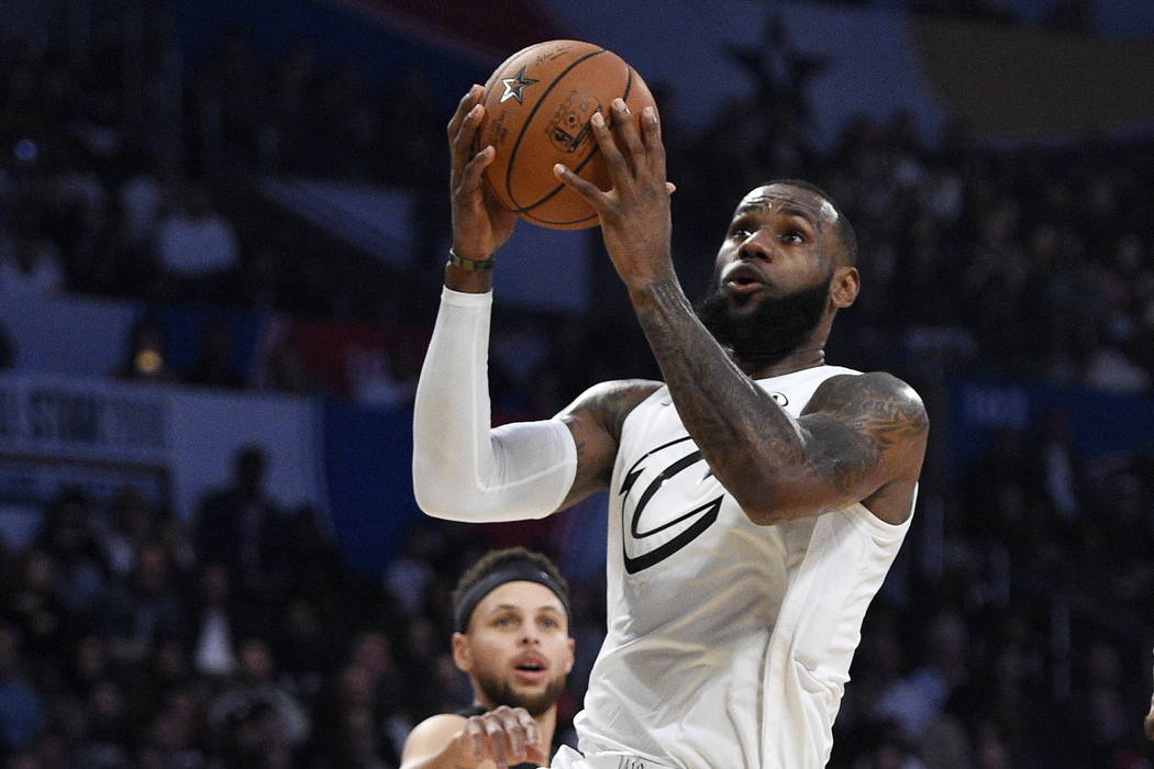 Team LeBron's LeBron James, right, of the Cleveland Cavaliers, shoots as Team Stephen's Stephen Curry, of the Golden State Warriors, defends during the first half of an NBA All-Star basketball gam ...