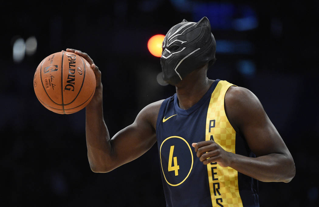"Indiana Pacers' Victor Oladipo gets ready for a dunk while wearing a mask from the movie ""Black Panther"" during the NBA All-Star basketball slam dunk contest Saturday, Feb. 17, 2 ..."