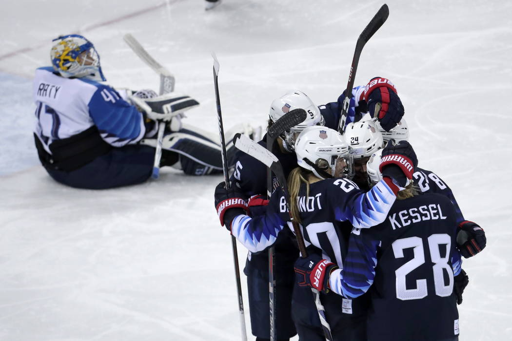 Players from the United States celebrate after Dani Cameranesi (24), of the United States, scores a goal against Finland during the third period of the semifinal round of the women's hockey game a ...