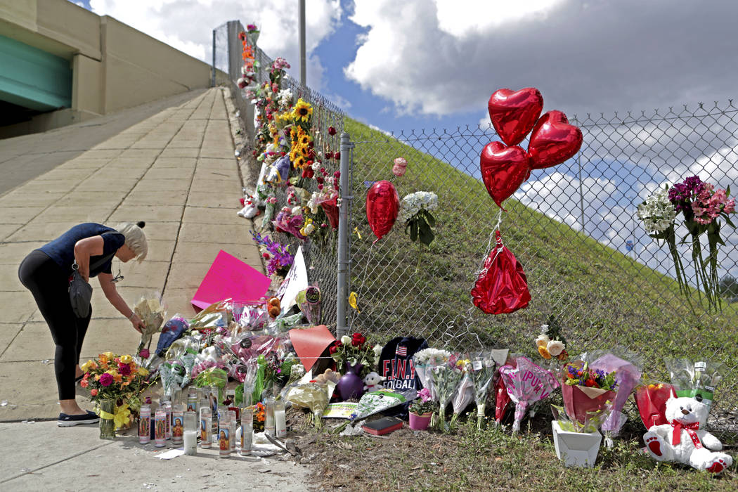 Ann Newman of Deerfield Beach, Fla., a retired Broward County teacher, places flowers at a makeshift memorial at Marjory Stoneman Douglas High School in Parkland, Fla., Sunday, Feb. 18, 2018. (Joh ...