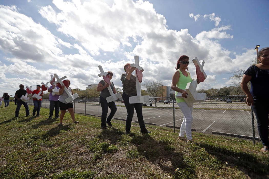 Volunteers carry 17 crosses to be placed outside the Marjory Stoneman Douglas High School in Parkland, Fla., Sunday, Feb. 18, 2018, where 17 people were killed in a mass shooting on Wednesday. (Ge ...