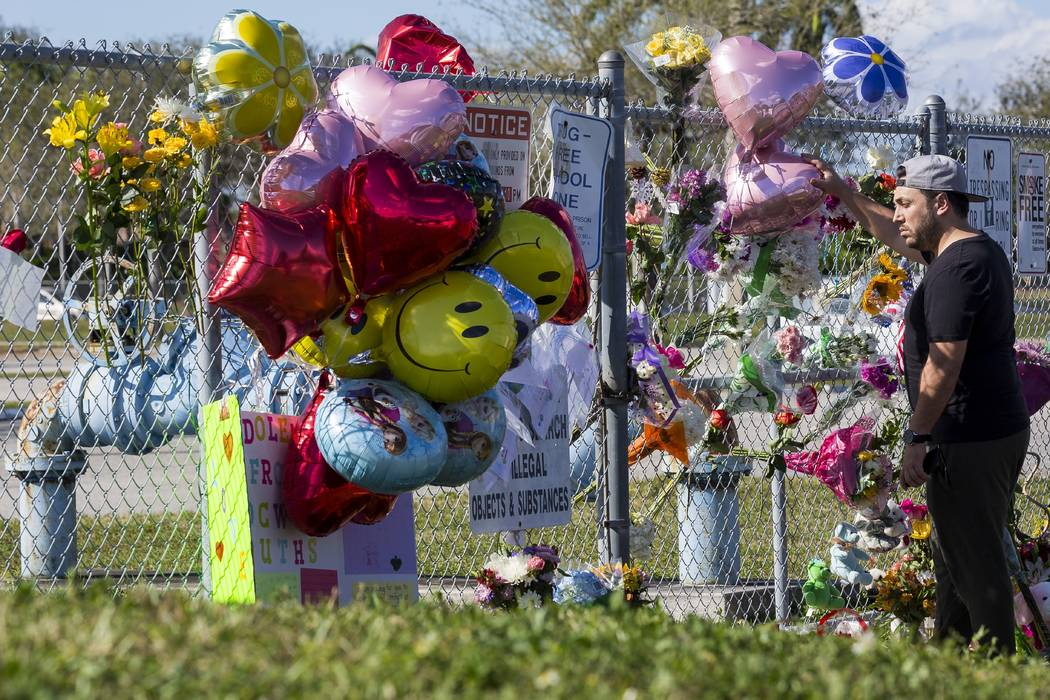 Gene Hochman, 36, reacts as he mourns near a makeshift memorial created by the community members outside of Marjory Stoneman Douglas High School in Parkland, Fla., on Sunday, Feb. 18, 2018. A gunm ...