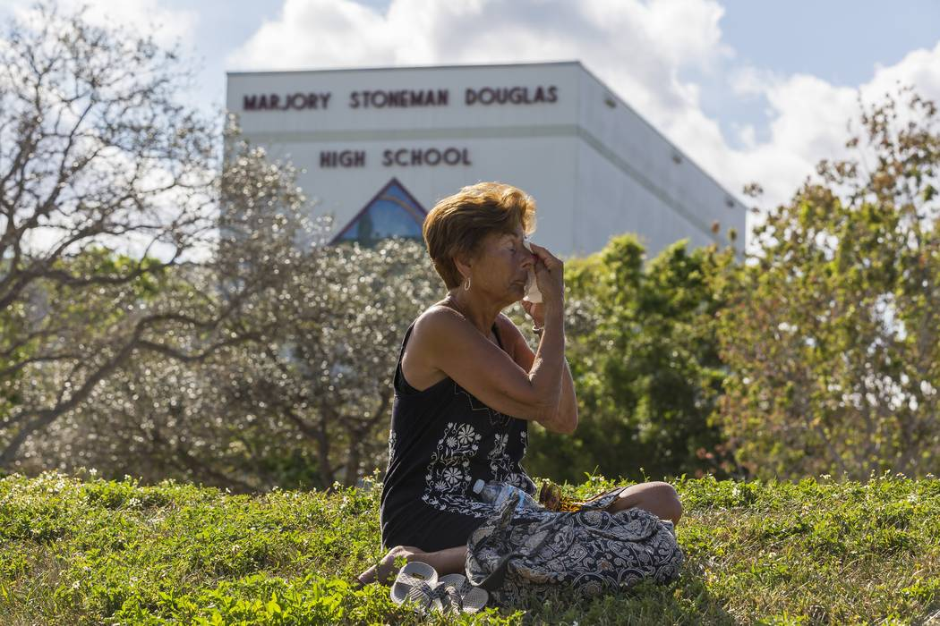 Diane Cappelli wipes her face as she mourns in front of Marjory Stoneman Douglas High School in Parkland, Fla., on Sunday, Feb. 18, 2018. A gunman entered the school last Wednesday and killed 17 s ...