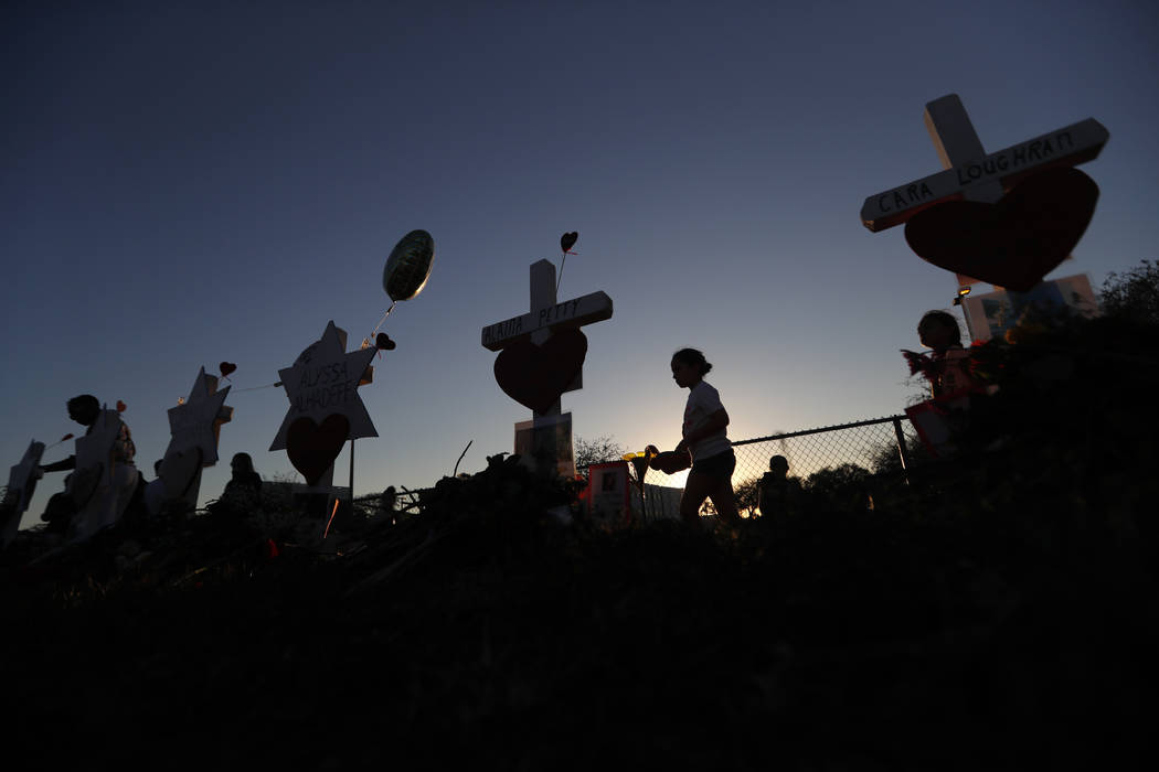 People walk among a makeshift memorial outside the Marjory Stoneman Douglas High School, where 17 students and faculty were killed in a mass shooting on Wednesday, in Parkland, Fla., Sunday, Feb.  ...