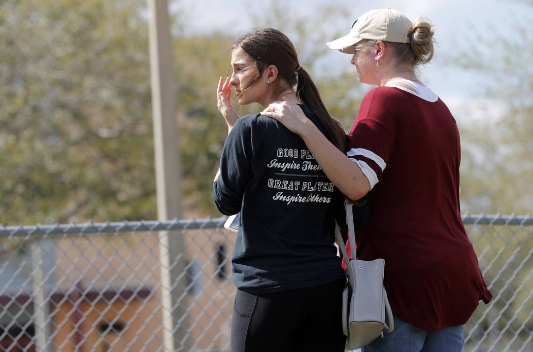 Hadley Sorensen, 16, a student at Marjory Stoneman Douglas High School, is comforted by her mother, Stacy Sorensen, outside the school in Parkland, Fla., Sunday, Feb. 18, 2018, where 17 people wer ...