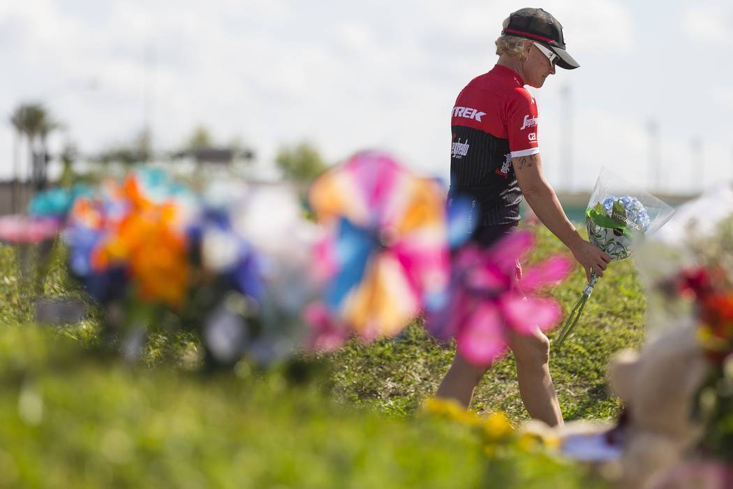 Mourners bring flowers to a makeshift memorial created by community members outside of Marjory Stoneman Douglas High School in Parkland, Fla., on Sunday, Feb. 18, 2018. A gunman entered the school ...