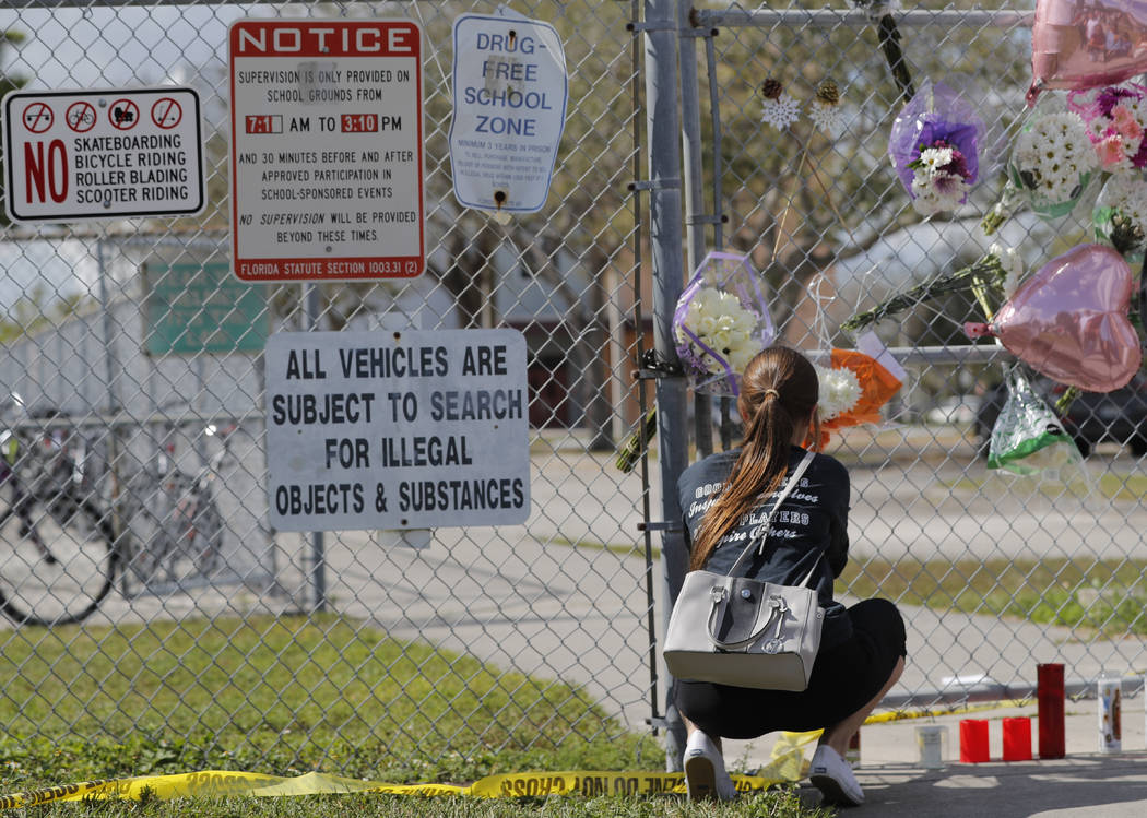 Hadley Sorensen, 16, a student at Marjory Stoneman Douglas High School, places flowers outside the school in Parkland, Fla., Sunday, Feb. 18, 2018, where 17 people were killed in a mass shooting o ...