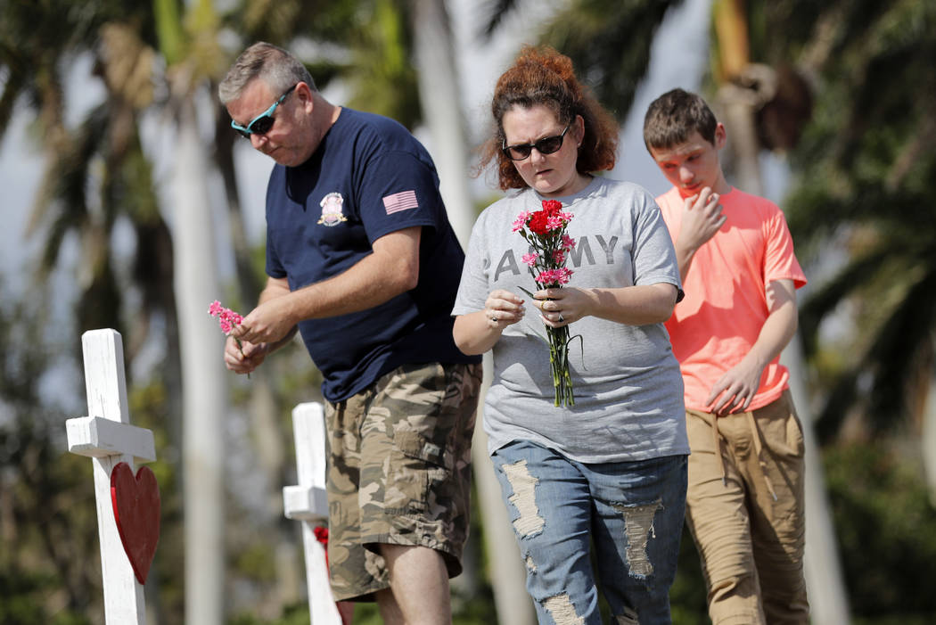 Bryan and Amber Gruzenksy place flowers on crosses with their son Joshua, 14, outside the Marjory Stoneman Douglas High School in Parkland, Fla., Sunday, Feb. 18, 2018, where 17 people were killed ...