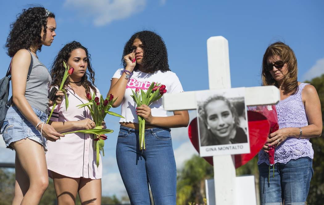 Tatana Hobson 14, left, Annia Hobson 13, and Leilany Canate, 16, mourn in front of Marjory Stoneman Douglas High School in Parkland, Fla., on Sunday, Feb. 18, 2018. (Matias J. Ocner/Miami Herald v ...