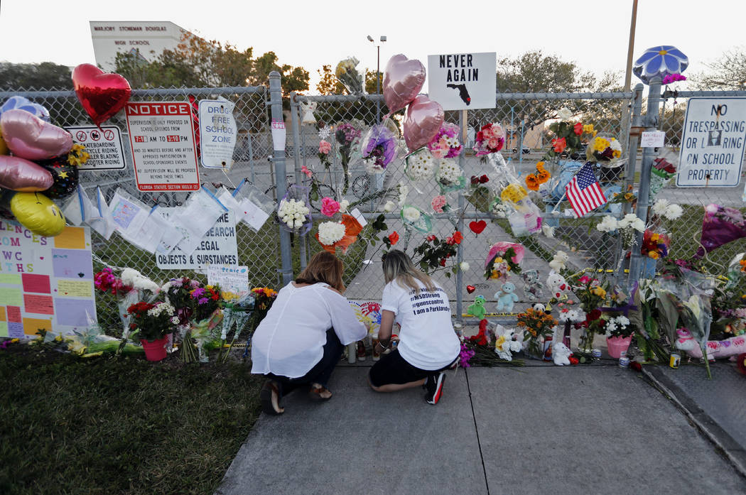 People light candles at a makeshift memorial outside Marjory Stoneman Douglas High School, where 17 students and faculty were killed in Wednesday's mass shooting in Parkland, Fla., Sunday, Feb. 18 ...