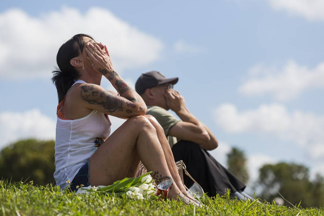 Stacey Sindon, 51, mourns in front of Marjory Stoneman Douglas High School in Parkland, Fla., on Sunday, Feb. 18, 2018. A gunman entered the school last Wednesday and killed 17 students and teache ...