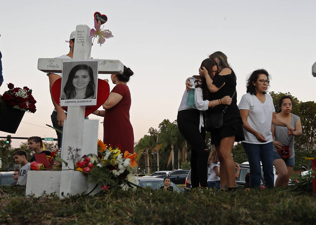 Magaly Newcomb, right comforts her daughter Haley Newcomb, 14, a student at Marjory Stoneman Douglas High School, at a makeshift memorial outside the school, in Parkland, Fla., Sunday, Feb. 18, 20 ...