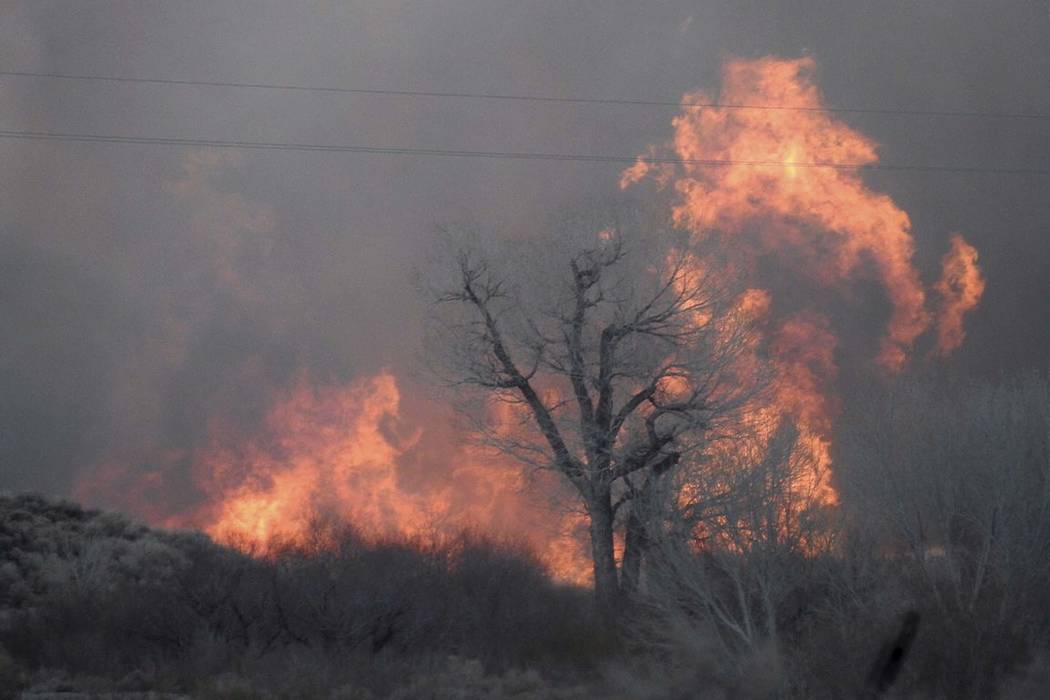 Smoke rising from wildfires near Bishop, Calif., Sunday, Feb. 18, 2018. A wind-driven wildfire in rural central California forced mandatory evacuations and threatened hundreds of buildings Monday, ...