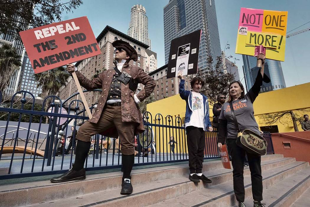 Konstantine Anthony, left, joins other grassroots protestors during a rally against gun violence in downtown Los Angeles on Monday, Feb. 19, 2018. Hundreds of sign-carrying, chanting protesters ha ...