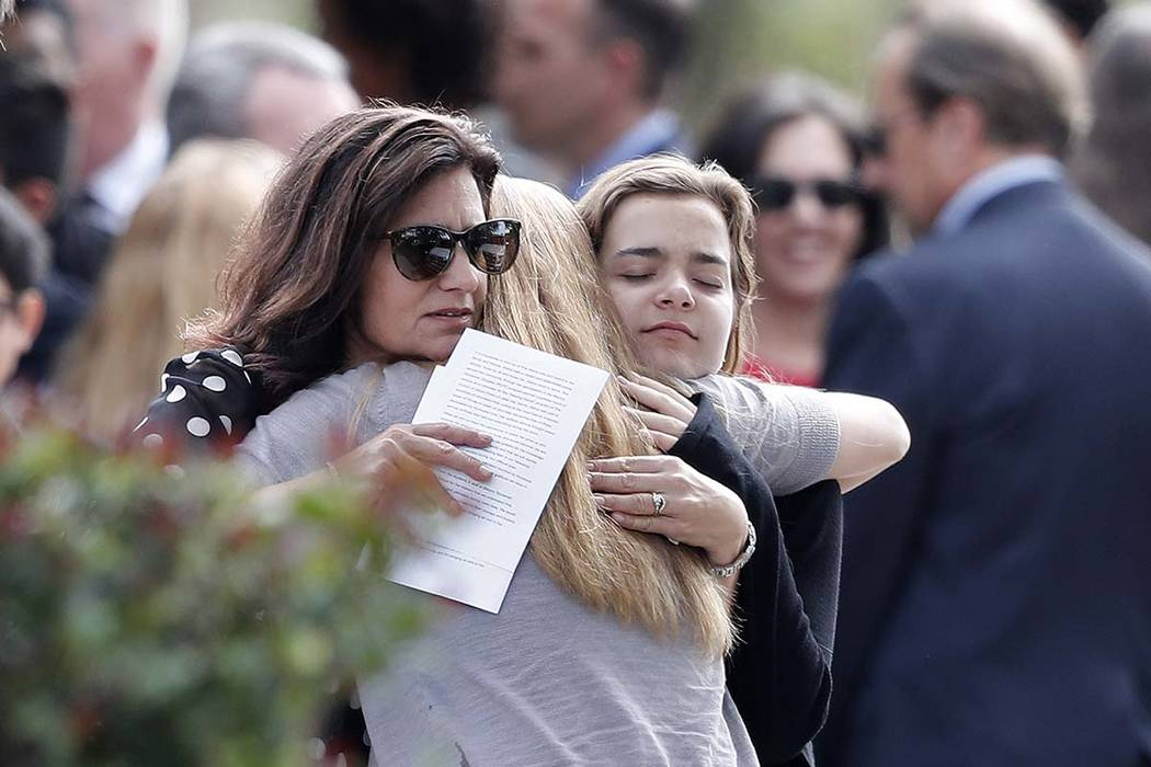 Mourners hug as they leave the funeral of Alaina Petty, in Coral Springs, Florida, Monday, Feb. 19, 2018.  Petty was a victim of Wednesday's mass shooting at Marjory Stoneman Douglas High School.  ...