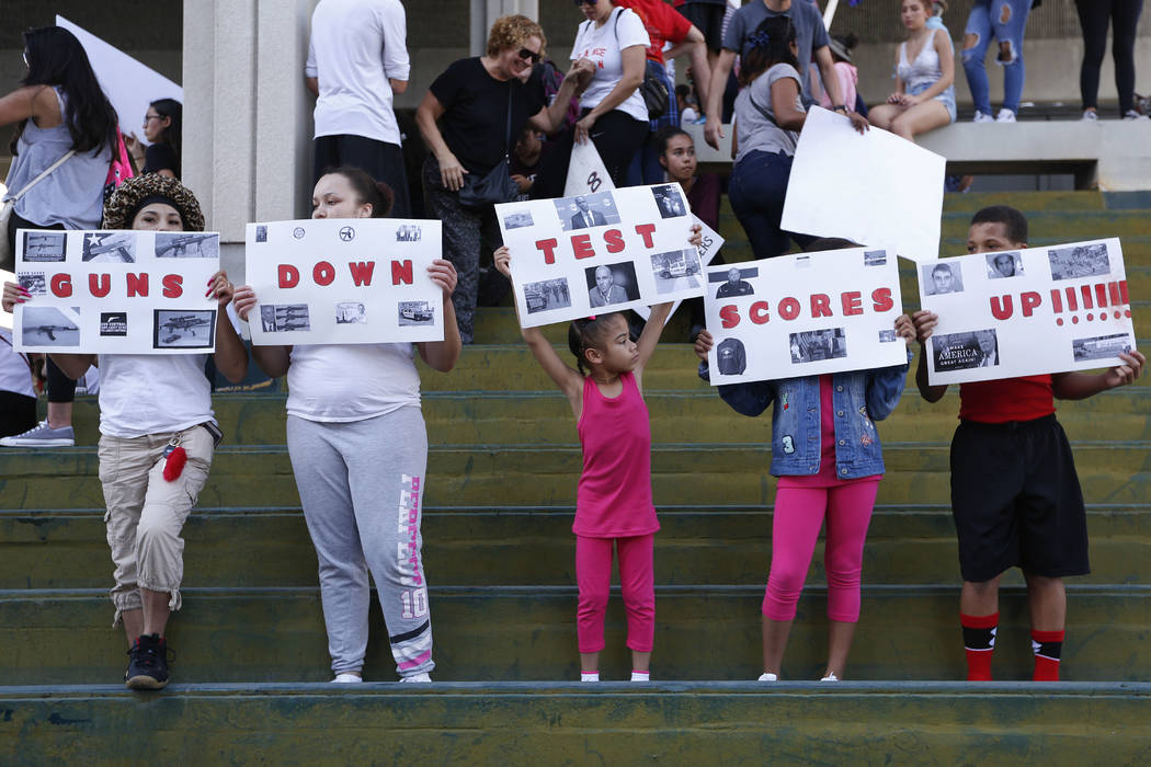 """A group of people hold signs that read """"Guns Down Test Scores UP"""" during a protest against guns on the steps of the Broward County Federal courthouse in Fort Lauderdale, Fla., on Saturday, Feb. 17 ..."""