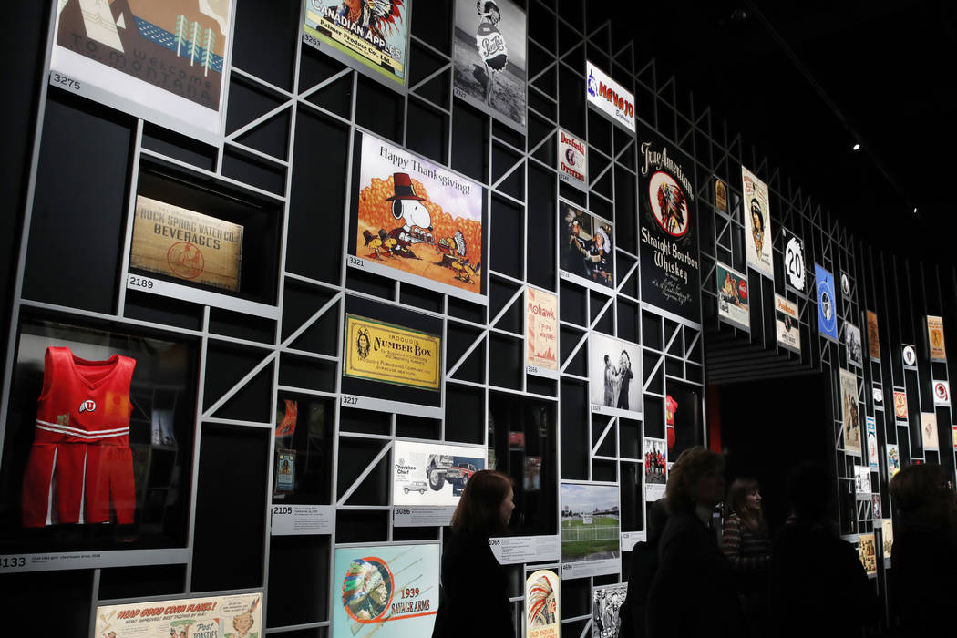 """People look at the """"Americans"""" exhibit at the Smithsonian's National Museum of the American Indian, Friday, Feb. 9, 2018, in Washington. A new exhibit uses images of Natives to show how the popula ..."""