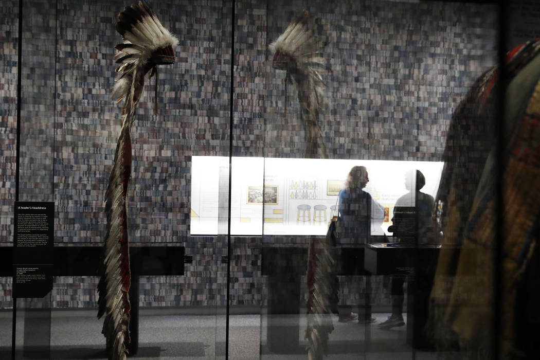 """People look at a section of the """"Americans"""" exhibit that explores the historical context of the Battle of Little Bighorn, at the Smithsonian's National Museum of the American Indian, Friday, Feb.  ..."""