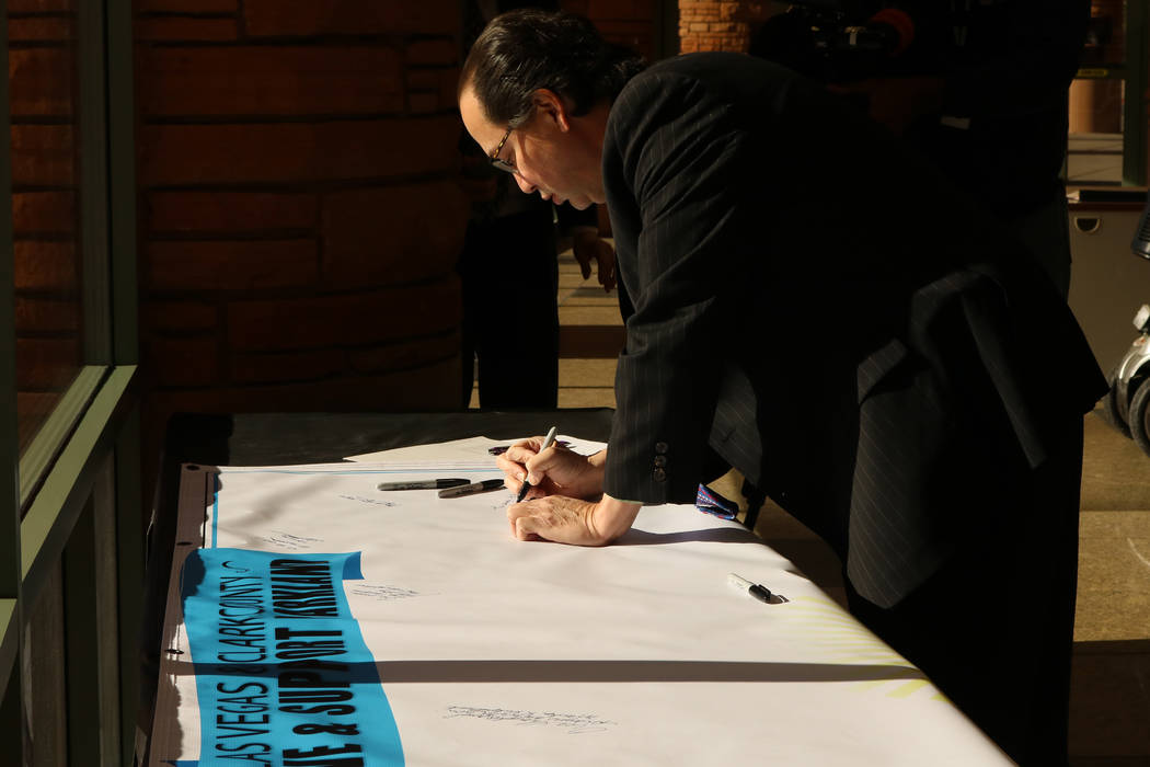 Thomas Chee signs a banner for Parkland, Fla. residents at the Clark County Government Center in Las Vegas, Tuesday, Feb. 20, 2018.  A school shooting left 17 dead in Park ...