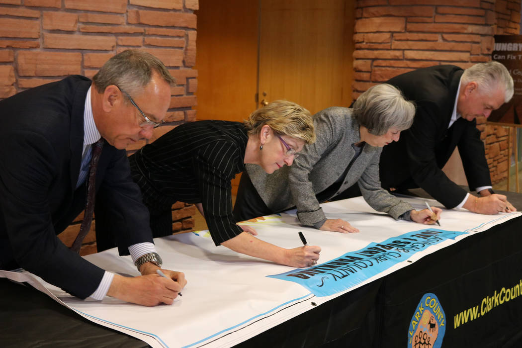 Clark County Commissioners James B. Gibson, left, Chris Giunchigliani, Susan Brager, and Steve Sisolak sign a banner for Parkland, Fla. residents at the Clark County Government Center in Las  ...