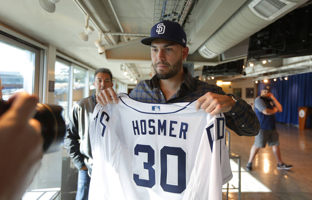 San Diego Padres baseball player Eric Hosmer poses with his jersey after an introductory press conference in Peoria, Ariz., Tuesday, Feb. 20, 2018. K.C. Alfred/The San Diego Union-Tribune via AP)