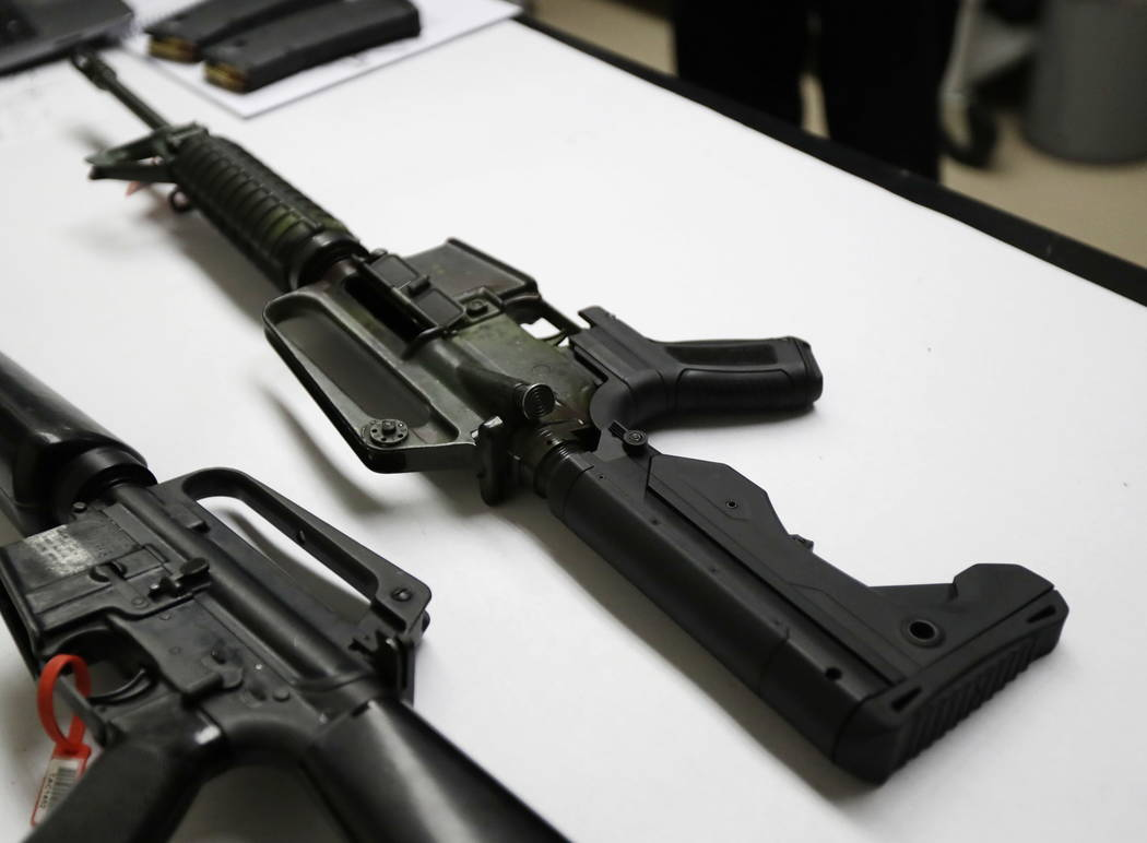 In this Jan. 11, 2018 photo, a semi-automatic rifle at right that has been fitted with a so-called bump stock device to make it fire faster sits on a table at the Washington State Patrol crime lab ...