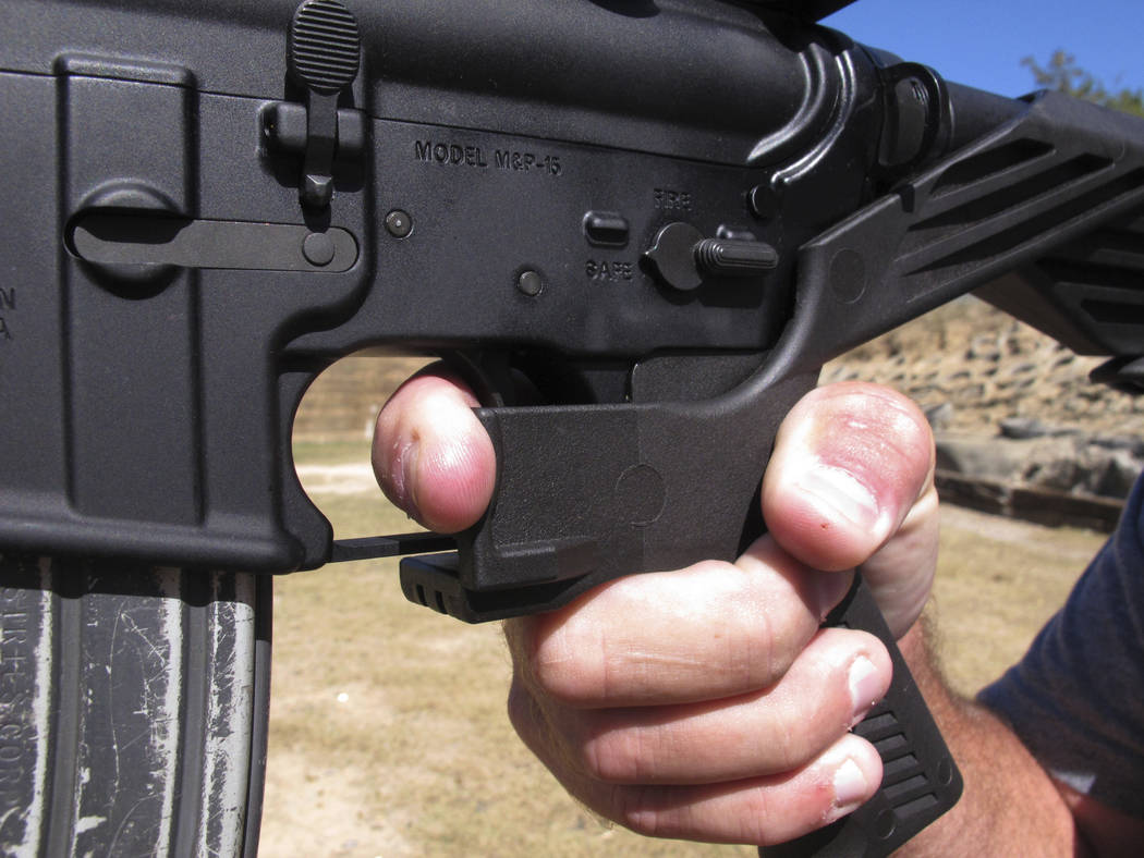 FILE - In this Oct. 4, 2017, file photo, shooting instructor Frankie McRae demonstrates the grip on an AR-15 rifle fitted with a bump stock at his 37 PSR Gun Club in Bunnlevel, N.C. The largest gu ...