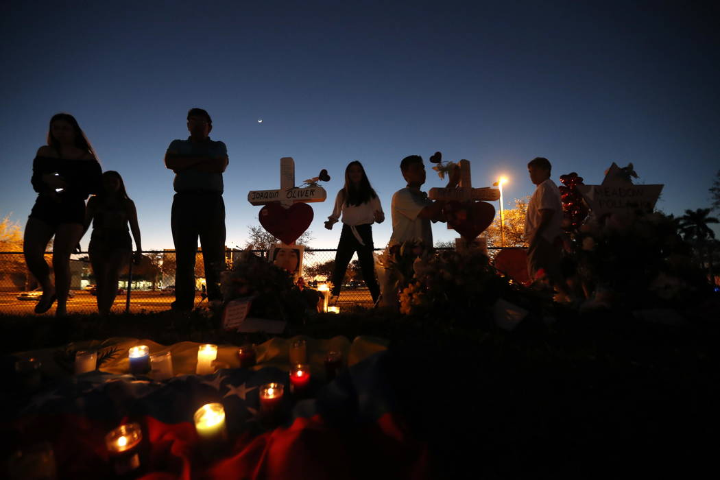 People visit a makeshift memorial outside Marjory Stoneman Douglas High School, where 17 students and faculty were killed in Wednesday's mass shooting in Parkland, Fla., Sunday, Feb. 18, 2018. Nik ...