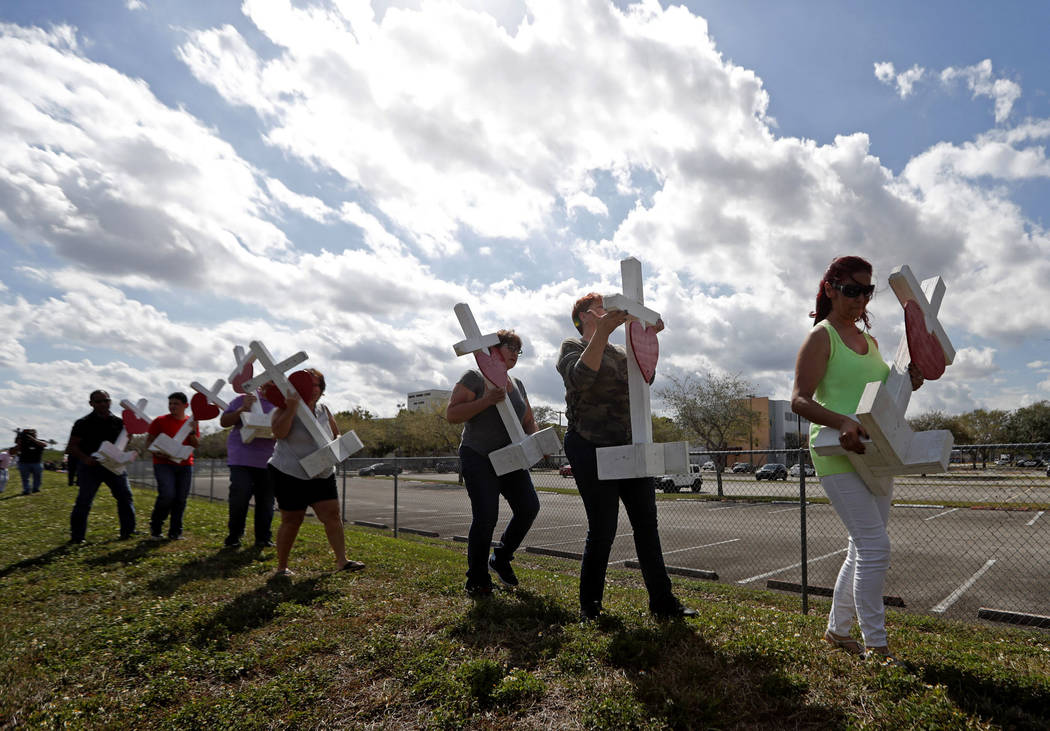 Volunteers help carry 17 crosses to be placed outside the Marjory Stoneman Douglas High School in Parkland, Fla., Sunday, Feb. 18, 2018, where 17 people were killed in a mass shooting on Wednesday ...