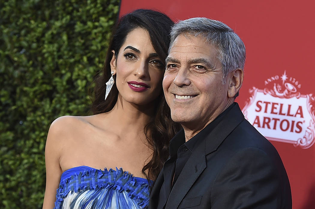 """FILE - In this Oct. 22, 2017 file photo, Amal Clooney and George Clooney arrive at the premiere of """"Suburbicon"""" in Los Angeles. George and Amal Clooney are donating $500,000 to s ..."""
