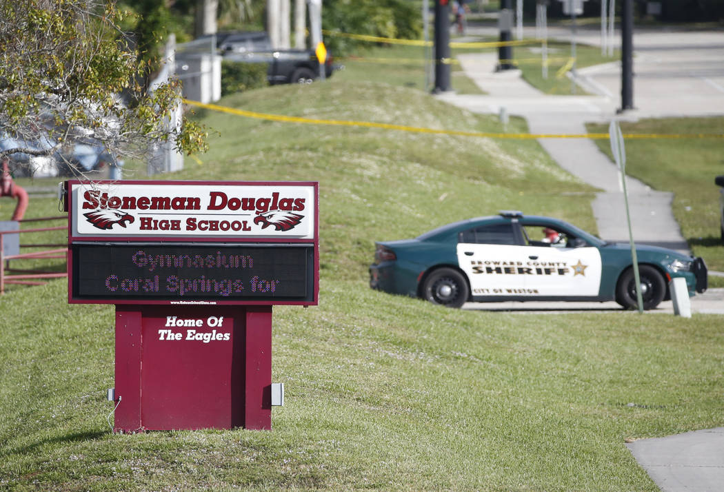 Law enforcement officers block off the entrance to Marjory Stoneman Douglas High School, Thursday, Feb. 15, 2018 in Parkland, Fla.  Nikolas Cruz was charged with 17 counts of premeditated murder o ...