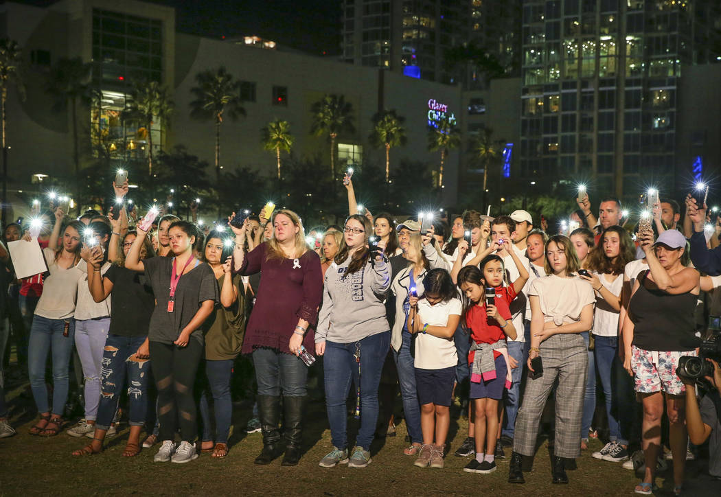 People raise their lights during a vigil at Curtis Hixon Park in downtown Tampa, Fla., Monday, Feb. 19, 2018, honoring victims of Wednesday's shooting at Marjory Stoneman Douglas High School in Pa ...