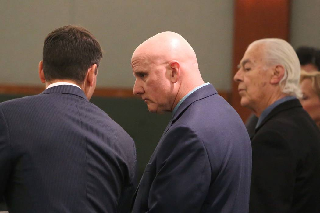 Las Vegas Metro Police officer, Lt. James Melton, center, appears in court at the Regional Justice Center on Wednesday, Feb. 21, 2018, in Las Vegas. Melton faces 14 felony counts, including theft, ...