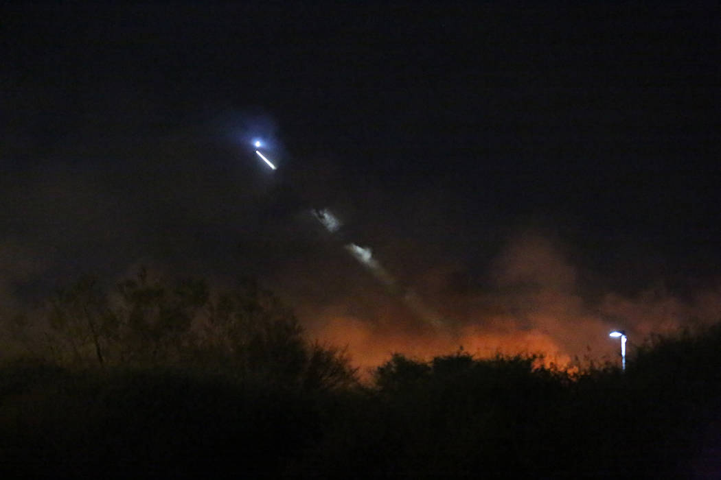 A helicopter spotlight cuts through the smoke of a fire at Clark County Wetlands Park on Tuesday, February 20, 2018. Michael Quine/Las Vegas Review-Journal @Vegas88s