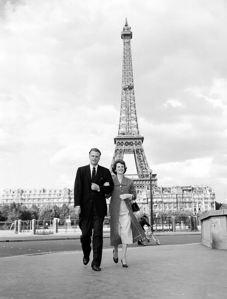 American evangelist Billy Graham and his wife Ruth take a stroll in Paris after his arrival for a five-day crusade, June 4, 1955. The Eiffel Tower rises in the background. (AP Photo)