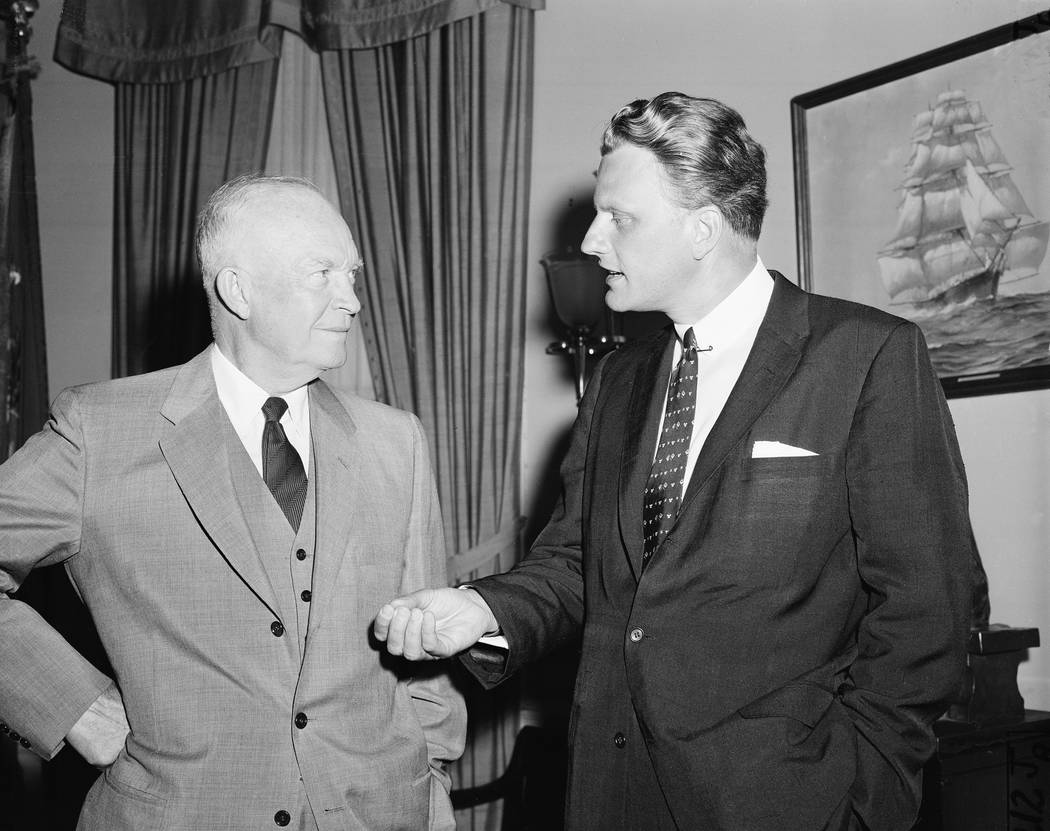 Evangelist Billy Graham, right, talks with U.S. President Dwight Eisenhower during a visit at the White House in Washington, D.C., May 10, 1957.  (AP Photo)