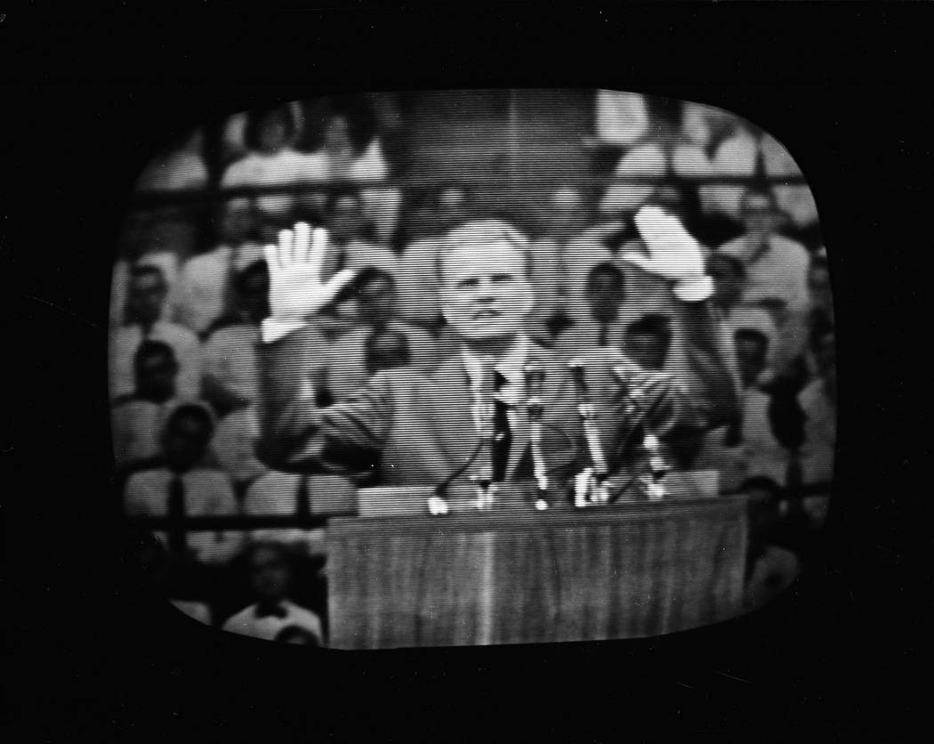 The Rev. Billy Graham appears on a television screen during a live telecast of his crusade at New York's Madison Square Garden, that a standing-room-only crowd of over 19,000 attended, June 1, 195 ...