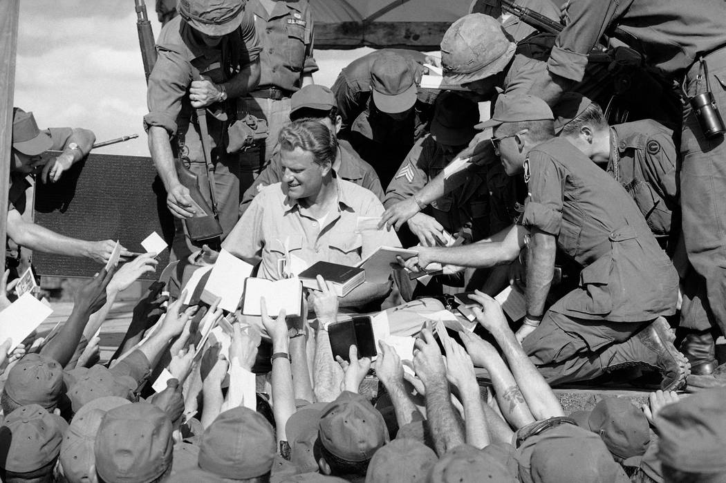 Scores of American GIs reach up to shake the hand and get his autograph after evangelist Billy Graham spoke to some 5,000 combat soldiers at the long Binh headquarters of field force II north of S ...