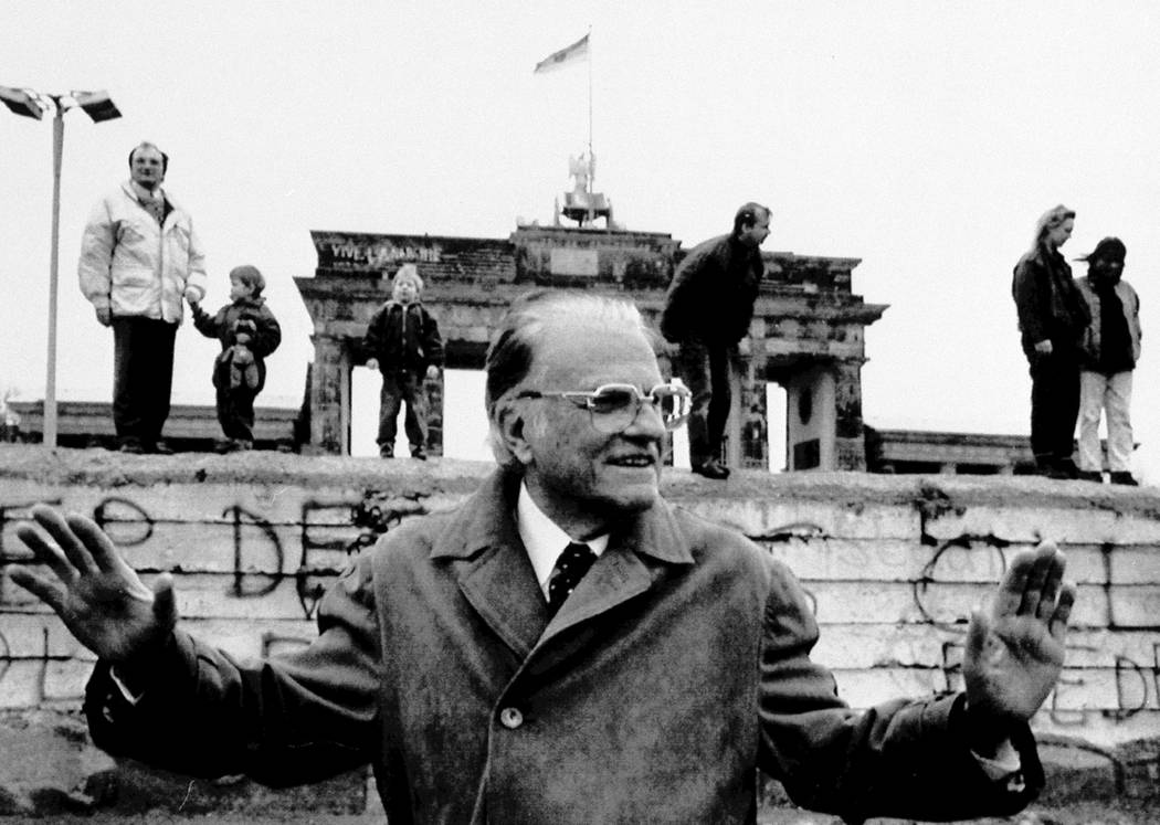 Rev. Billy Graham poses in front of the Brandenburg Gate, March 8, 1990. (AP Photo/Mathias Krause)