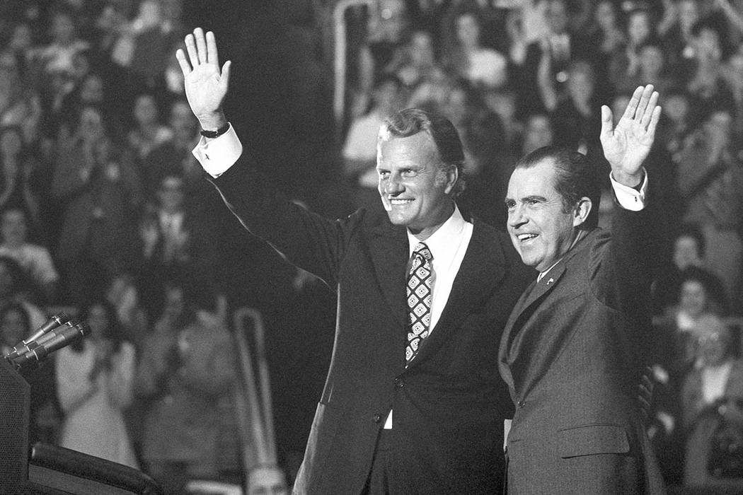 In this Oct. 16, 1971 file photo, evangelist Billy Graham and President Richard Nixon wave to a crowd at ceremonies honoring Graham at Charlotte, N.C.  Graham, who long suffered from cancer, pneum ...