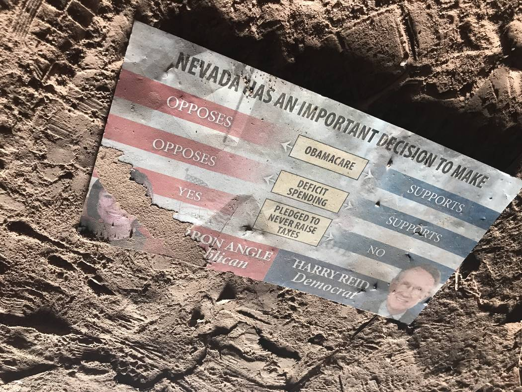 A campaign mailer from then-Sen. Harry Reid's 2010 senate race collects dust on the floor of an abandoned mine shaft near Fort Apache and Warm Springs roads on Wednesday, Feb. 21, 2018.(Henry Br ...