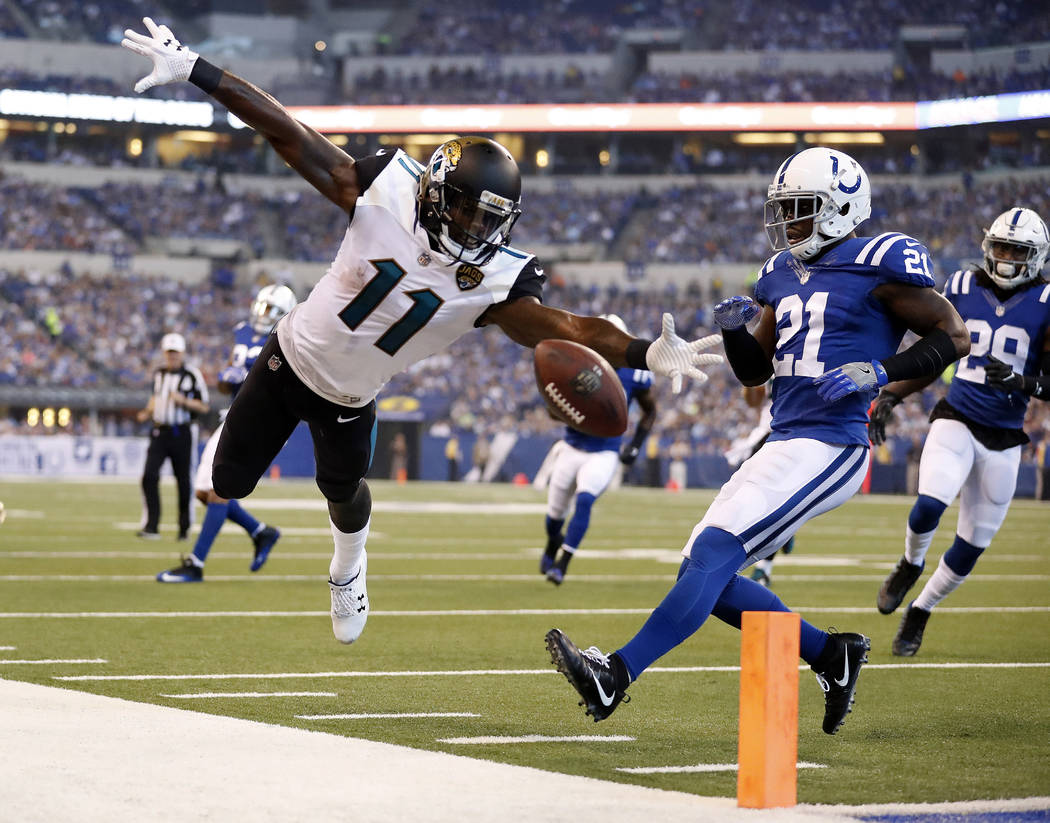 Jacksonville Jaguars wide receiver Marqise Lee (11) looses the ball out-of-bounds after a catch in front of Indianapolis Colts cornerback Vontae Davis (21) during the first half NFL football game  ...
