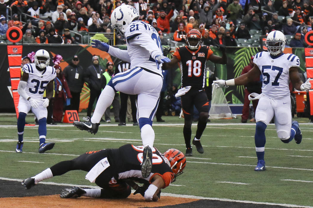 Cincinnati Bengals defensive end Michael Johnson, bottom, catches a touchdown pass against Indianapolis Colts cornerback Vontae Davis (21) in the second half of an NFL football game, Sunday, Oct.  ...