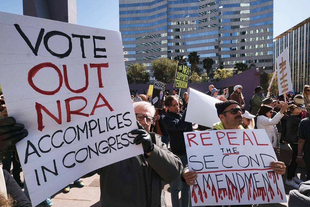 Protesters join in on a grassroots movement during a rally against gun violence in downtown Los Angeles on Monday, Feb. 19, 2018. Hundreds of sign-carrying, chanting protesters have converged on a ...